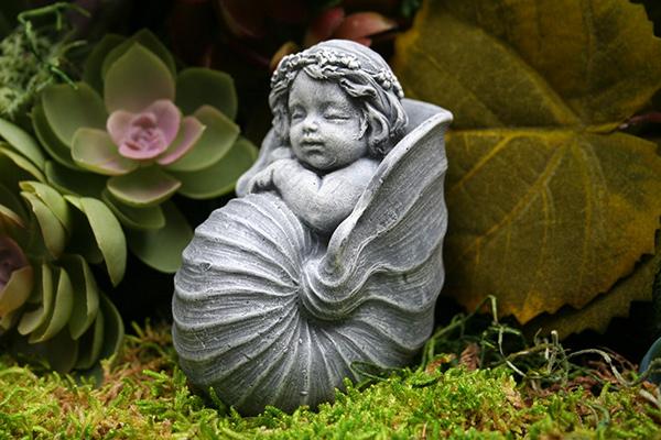 Esculturas para jardim que impressionam - boneca dentro de um búzio