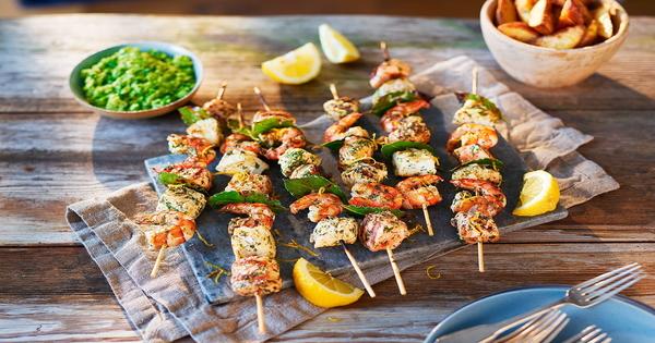 Uma fantástica refeição saudável espetadas de salmão e bacalhau e uma salada mediterrânea - espetadas
